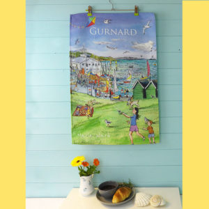 tea towel featuring gurnard green with girl flying kite on the Isle of Wight